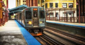 Train on elevated tracks within buildings at the Loop, Chicago City Center - Warm Sunset Artistic Effect - Chicago, Illinois. USA Royalty Free Stock Photography