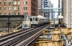 Train on elevated tracks within buildings at the Loop, Glass and Steel bridge between buildings - Chicago City Center - Chicago, I. Llinois, USA Stock Image