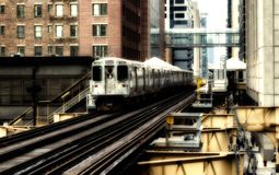 Train on elevated tracks within buildings at the Loop, Glass and Steel bridge between buildings - Chicago City Center - Sepia Glow. Artistic Effect - Chicago Stock Image