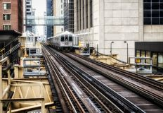 Train on elevated tracks within buildings at the Loop, Glass and Steel bridge between buildings - Chicago City Center - Soft and G. Rainy Artistic Effect Stock Image