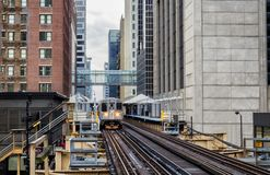 Train on elevated tracks within buildings at the Loop, Glass and Steel bridge between buildings - Chicago. City Center - Chicago, Illinois, USA Stock Images