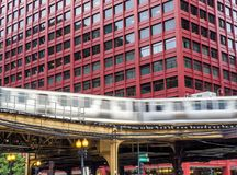 Train on elevated tracks within buildings at the Loop, Glass and Steel bridge between buildings - Long Exposure. Chicago City Center - Chicago, Illinois, USA Stock Image