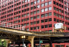Train on elevated tracks within buildings at the Loop, Glass and Steel bridge between buildings. Chicago City Center - Chicago, Illinois, USA Stock Image