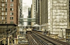 Train on elevated tracks within buildings at the Loop, Glass and Steel bridge between buildings - Chicago City Center - Black Gold. Artistic Effect - Chicago Stock Image