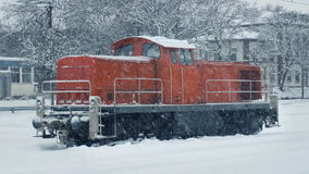 Train Engine In Heavy Snowfall. Red train engine in winter landscape with snow falling stock video footage