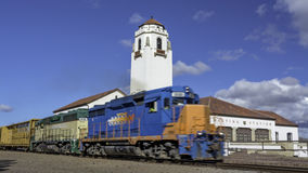 Train engine pulls its cars by the depot with blue sky Stock Images