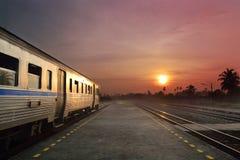 Train fonctionnant dans le coucher du soleil Photographie stock libre de droits