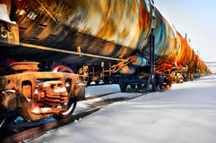 Train with fuel petrol tanks on the railway. Set of old tanks with oil and fuel transport by rail in winter Stock Photo