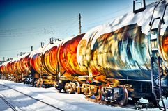 Train with fuel petrol tanks on the railway. Set of old tanks with oil and fuel transport by rail in winter Stock Photos