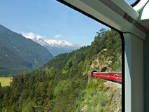 Train Glacier Express. World famous swiss train Glacier Express makes it's way over into a tunnel, seen from inside the train with wooded alpine mountains in the Stock Images