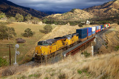 The train goes across the bridge. A large rail transportation of cargo containers Stock Image