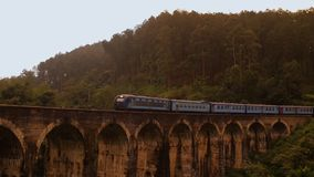 The train goes along the beautiful old bridge.  stock footage
