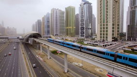 The train goes over the viaduct, along the highway among the skyscrapers in Dubai, UAE stock video