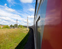 Train goes by rail in summer day Royalty Free Stock Photography