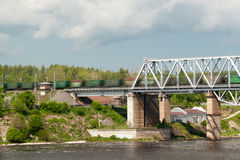 The train goes on the railway bridge through the river Royalty Free Stock Images