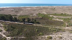 Train goes through the Ria Formosa to the beach a barrel in the background of the sea. stock footage