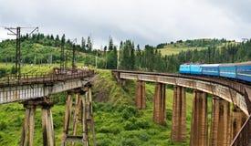 Train going across the bridge in the Carpathians Stock Photo