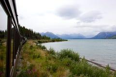 Train going along mountain lake in Yukon, Canada. A train travels along a lake in the mountains with wildflowers all around. Taken on the White Pass and Yukon Stock Photography