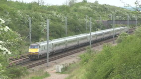 Train going through a cutting. Diesel train travailing  through a cutting on the main London to Scotland railway line stock footage