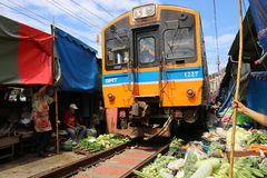 Train going through Maeklong Train Market, a unique market where vegetable sellers ply their wares next to the railway track. Stock Photos
