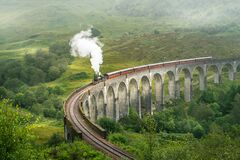 Train going over the Glenfinnan railway viaduct in Scotland, UK