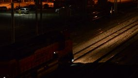 Train headlight lighting the tracks. A commuter train passes, then the headlight of a freight train lights the tracks stock video footage