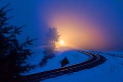 A train headlight pierces the dusk in Montana Royalty Free Stock Photography