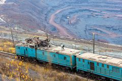Train at the iron ore opencast mine is going for loading iron Stock Image