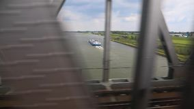 Train journey window view. Train journey in slow motion crossing canal waterway in the Netherlands stock footage