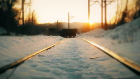 Train leaves in the winter sunset in the distance. HD stock footage