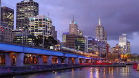 Train leaving CBD of a city at sunset. Melbourne, Australia - Sep 18, 2015: 4k video of a train leaving Melbourne CBD at sunset with office buildings in the stock video footage