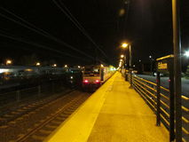 Train leaving Edison train station at night, NJ USA. Stock Photo