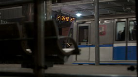 Train leaving metro station in Moscow. Train leaving Kuntsevskaya metro station in Moscow, Russia. Chairs for waiting passengers in foreground stock footage