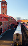 Train leaving old rail station platform. The tail of the passing away train from the platform of the old historic rail station with a number of brick buildings royalty free stock photo