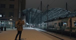 Train leaving the station at night and man making video on mobile. HELSINKI, FINLAND - JANUARY 07, 2017: Central railway station at winter night. Passenger train stock footage