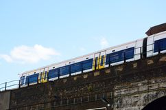 Train leaving station on viaduct Royalty Free Stock Image