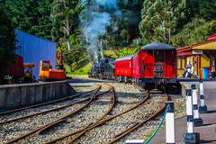 Train leaving the station, Wellington City, Wellington, New Zealand. A steam locomotive with a red baggage car and a red caboose pulls out of the train station Royalty Free Stock Images