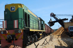 Train loading on career by sand. Loading of a train by a dredge on career by sand Royalty Free Stock Photography