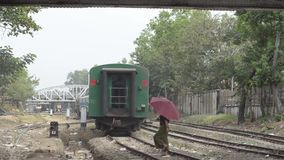 TRAIN LOCOMOTIVE: Green passenger train down tracks, umbrella lady nearby. TRAIN LOCOMOTIVE: Green passenger train heads down tracks, umrella lady nearby. From stock footage