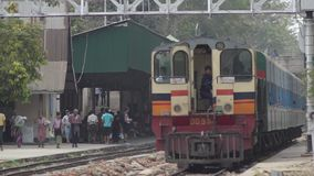TRAIN LOCOMOTIVE: Medium shot of striped train passing. With passengers visible at station in background. From ' Diesel Train in Myanmar  (Asia) ', one of many stock video