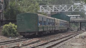 TRAIN - LOCOMOTIVE: Old green commuter train at far platform. TRAIN LOCOMOTIVE: Old green commuter train at far platform, before departing down tracks. From ' stock video footage