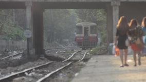 TRAIN LOCOMOTIVE: Platform level view of distant train approaching station. With several passengers walking on platform. From ' Diesel Train in Myanmar  (Asia stock footage