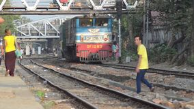 TRAIN LOCOMOTIVE: Red and blue train approaches among pedestrians. TRAIN LOCOMOTIVE: Red and blue train approaches while pedestrians cross and walk along tracks stock video footage
