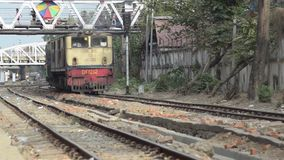 TRAIN - LOCOMOTIVE: Track level view of yellow train approaching with footbridge. TRAIN LOCOMOTIVE: Track level view of yellow train approaching with footbridge stock footage