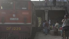 TRAIN LOCOMOTIVE: Train approaches underpass-passengers on platform. TRAIN LOCOMOTIVE: Train approaches through underpass with passengers on platform. From ' stock footage