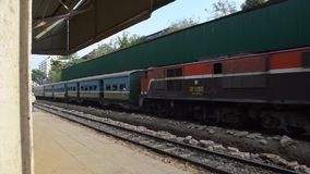 TRAIN LOCOMOTIVE:  train passes with porters carrying bags on head. TRAIN LOCOMOTIVE:  Oblique wide shot of train passing with porters carrying bags on their stock video footage