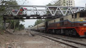TRAIN LOCOMOTIVE: Wide shot red train passes under pedestrian foot bridge. From ' Diesel Train in Myanmar  (Asia) ', one of many clips from this series from stock video footage