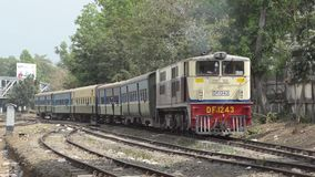 TRAIN - LOCOMOTIVE: Yellow and red train arrives and passes. TRAIN LOCOMOTIVE: Yellow and red train arrives and passes, pulling a motley group of cars behind stock footage