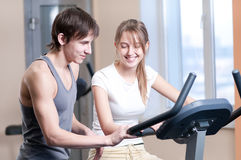 Train on machine in a gym. Woman and man train on machine in a gym assisted by personal instructor stock images