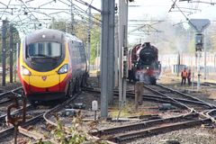 Train moderne de Pendolino passant un vieux train de vapeur Photo libre de droits
